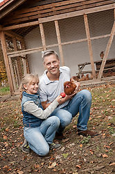 Father and daughter with chicken on organic farm