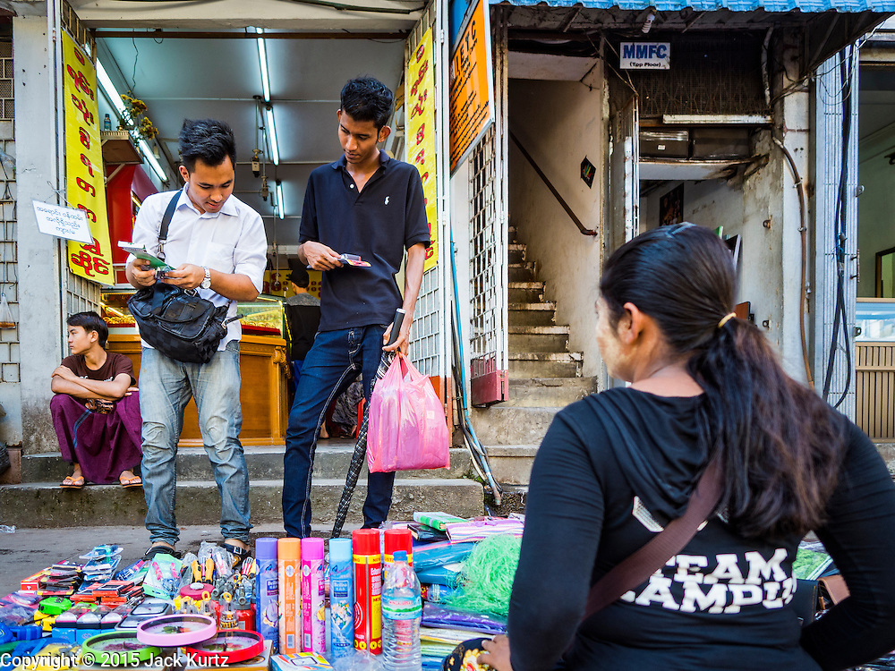 """06 NOVEMBER 2015 - YANGON, MYANMAR:  Men look at tools being sold at an informal street shop in Yangon. Some economists think Myanmar's informal economy is larger than the formal economy. Many people are self employed in cash only businesses like street food, occasional labor and day work, selling betel, or working out of portable street stalls, doing things like luggage repair. Despite reforms in Myanmar and the expansion of the economy, most people live on the informal economy. During a press conference this week, Burmese opposition leader Aung San Suu Kyi said, """"a great majority of our people remain as poor as ever.""""      PHOTO BY JACK KURTZ"""
