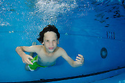 Young boy holds her breath while swimming underwater
