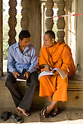 19 MARCH 2006 - SIEM REAP, SIEM REAP, CAMBODIA: A student and a Buddhist monk talk about the history of the Angkor Wat complex near Siem Reap, Cambodia in the main complex of Angkor Wat. Cambodian authorities estimate that more than one million tourists will visit Angkor Wat in 2006, making it the leading tourist attraction in Cambodia by a large margin. The temple is also a leading center of Buddhist worship in Cambodia.   Photo by Jack Kurtz / ZUMA Press