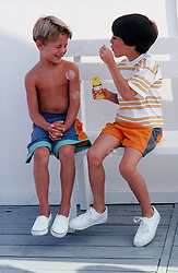 boy blowing bubbles towards another boy outdoors, playful, blowing bubbles, blond hair, black hair, summer, two boys together, shorts, fun, funny, play, 5-8 years old, shirtless, seated, adorable, cute, good clean fun, children, child