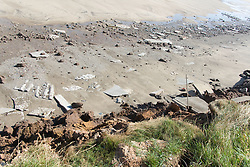 Concrete caravan bases on beach having fallen down eroded cliffs at Tunstall; East Yorkshire; England