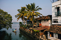Fort Kochi, India -- February 12, 2018: A fishing boat makes its way through a small neighborhood canal in Fort Kochi.
