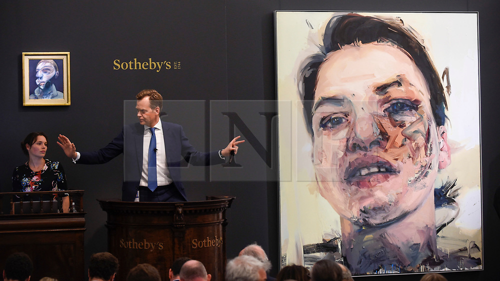 © Licensed to London News Pictures. 26/06/2019. LONDON, UK. Oliver Barker, Chairman, Sotheby's Europe, fields bids for (L) ''Self-Portrait'' by Francis Bacon, (Est. £15,000,000 - 20,000,000) which sold for a hammer price of £14,350,000 and (R) ''Shadow Head'' by Jenny Saville, (Est. £3,000,000 - 5,000,000) which sold for a hammer price of £3,500,000 at Sotheby's Contemporary Art Evening Sale in their New Bond Street galleries.  Photo credit: Stephen Chung/LNP