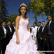 Quinceanera girl stands with her chamberlains outside