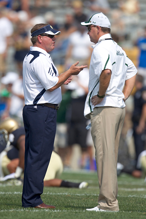 Notre Dame head coach Brian Kelly and South Florida head coach Skip Holtz talk during pregame action of NCAA football game between Notre Dame and South Florida.  The South Florida Bulls lead the Notre Dame Fighting Irish 16-0 at halftime in game at Notre Dame Stadium in South Bend, Indiana.  The game has been delayed due to rain storms and lightning in the area.