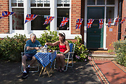 As the Coronavirus lockdown continues over the May Bank Holiday, the nation commemorates the 75th anniversary of VE Day Victory in Europe Day, the day that Germany officially surrendered in 1945 and in Dulwich, neighbours and residents emerge from their homes to party while still observing social distancing rules. A couple enjoy afternoon tea and cake beneath Union Jack bunting outside their home, on 8th May 2020, in London, England.