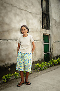 Philippines, Batanes. Portrait of Ivatan woman from a small village Chavayan on Sabtang Island standing in front of her house.