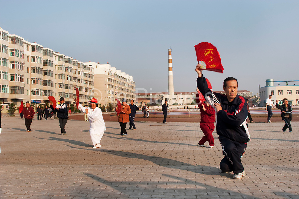 Chinese perform traditional Tai Chi sword dancing, fan dancing and taichi in a square at dawn in De Hui city, Jilin Province. North Eastern China.