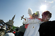 A woman hold a child dressed as an angel at the Catholic Fatima shrine in central Portugal 13 May 2004. Thousands of pilgrims converged on Fatima to celebrate the anniversary of the first apparition of the Virgin Mary to three shepherd children on 13 May 1917.PHOTO PAULO CUNHA/4SEE