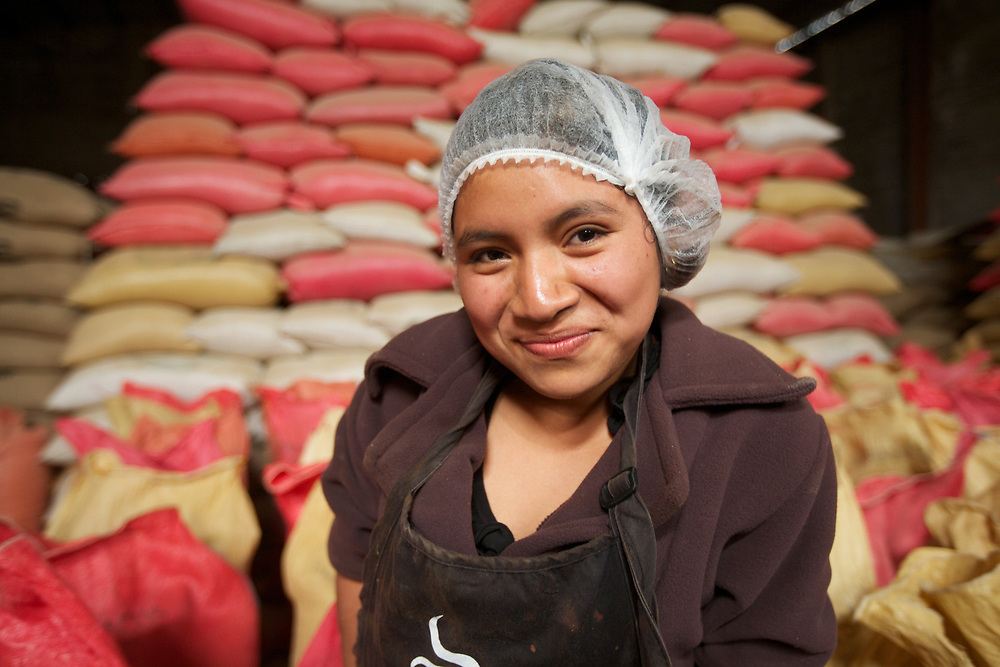 Elma Morales in front of stacks of coffee sacks ready for export at the FECCEG warehouse in Xela.