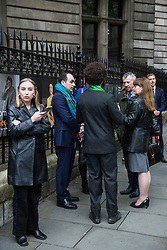 London, UK. 10 June, 2019. Guests observe activists from BP or not BP? disrupting the BP Portrait Award with a 'creative blockade' against oil sponsorship. The activists linked arms to block all entrances to the National Portrait Gallery, forcing guests to the awards to clamber over railings at the rear entrance to gain access, as well as creating live portraits outside the gallery of activists from West Papua, Mexico, Samoa and the US Gulf Coast fighting back against BP's pollution and climate devastation around the world. Energy company BP has sponsored the NPG's award for 30 years, but its high-profile involvement is attracting growing criticism for environmental reasons. A judge of this year's award, leading artist Gary Hume, has publicly called for the gallery to end its relationship with BP, as have eight former exhibitors including two former award winners Wim Heldens and Craig Wiley. Credit: Mark Kerrison/BP or not BP?