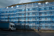 Social housing under refurbishment, covered in scaffolding and blue gauze in Wapping, London, England, United Kingdom.
