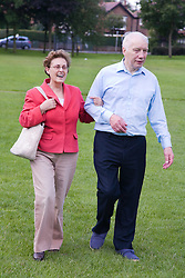 Older couple walking through the park together,