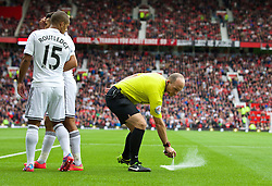 16.08.2014, Old Trafford, Manchester, ENG, Premier League, Manchester United vs Swansea City, 1. Runde, im Bild Referee Mike Dean sprays foam onto the pitch // 15054000 during the English Premier League 1st round match between Manchester United and Swansea City AFC at Old Trafford in Manchester, Great Britain on 2014/08/16. EXPA Pictures © 2014, PhotoCredit: EXPA/ Propagandaphoto/ David Rawcliffe<br /> <br /> *****ATTENTION - OUT of ENG, GBR*****