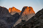 """Sunrise on Pingora Peak seen from Jackass Pass, Cirque of the Towers, Bridger Wilderness, Wind River Range, Bridger-Teton National Forest, Rocky Mountains, Wyoming, USA. We backpacked to Big Sandy Lake Campground (11 miles round trip with 1000 feet gain). Two hours before sunrise, I departed from Big Sandy Lake to reach Jackass Pass viewpoint for Cirque of the Towers and Lonesome Lake (6.5 miles round trip, 1860 ft gain) on the Continental Divide Trail. The Continental Divide follows the crest of the """"Winds"""". Mostly composed of granite batholiths formed deep within the earth over 1 billion years ago, the Wind River Range is one of the oldest mountain ranges in North America. These granite monoliths were uplifted, exposed by erosion, then carved by glaciers 500,000 years ago to form cirques and U-shaped valleys."""
