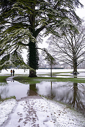© Licensed to London News Pictures 28/12/2020, Cirencester, UK. The Abbey grounds in Cirencester in the Cotswolds partially flooded by previous heavy rain are now covered in a layer of overnight snow. Photo Credit : Stephen Shepherd/LNP