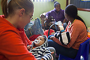 Female staff caring, interacting and feeding small babies at the Bigshoes Foundation Clinic, Johannesburg, South Africa.