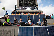 Extinction Rebellion climate change activists sit at the base of Nelsons Column in Trafalgar Square surrounded by solar panels which are powering activities in the area as sites around Westminster are blocked on 8th October 2019 in London, England, United Kingdom. Extinction Rebellion is a climate group started in 2018 and has gained a huge following of people committed to peaceful protests. These protests are highlighting that the government is not doing enough to avoid catastrophic climate change and to demand the government take radical action to save the planet.