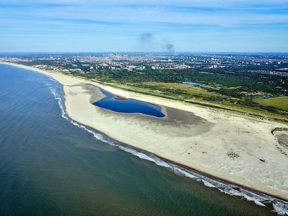 Nederland, Zuid-Holland, Gemeente Westland, 14-09-2019; Delflandse Kust ter hoogte van Ter Heijde en Monster, Den Haag aan de horizon. De Zandmotor is een kunstmatig schiereiland (landtong), ontstaan door het opspuiten van zand voor de kust. Wind, golven en stroming zullen het zand langs de kust in noordelijke richting verspreiden waardoor verderop langs de kust bredere stranden en duinen ontstaan. De zandmotor is een experiment in het kader van kustonderhoud en kustverdediging.<br /> Sand Engine, artificial peninsula build by the raising of sand for the coast (near the Hague at the horizon). Wind, waves and currents will distribute the sand along the coast yielding wider beaches and dunes along the coastline. The Sand Engine is a experiment for coastal maintenance of coastal defense.<br /> luchtfoto (toeslag op standard tarieven);<br /> aerial photo (additional fee required);<br /> copyright foto/photo Siebe Swart