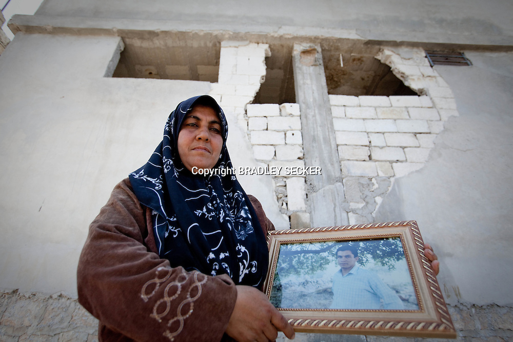 A mother holds a photograph of her son, who was killed whilst running from their family home into the mountains after the village was under attack by the Syrian military. Basheria, Idlib, Syria. 14/06/2012