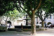 Small boy playing by fountain in shade of trees in town centre of Uzès, France, 1975