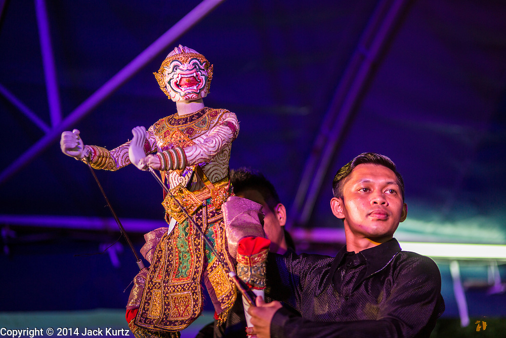 """24 JULY 2014 - BANGKOK, THAILAND: Traditional puppeteers perform the Ramakien (the Thai version of the Ramayana) with a Hanuman puppet at the happiness party in Bangkok. The Thai Junta is organizing a series of public events throughout Thailand meant to bolster public opinion. The events are called """"restoring happiness to the people"""" parties. They feature historic pageants, music, food, health checks and free haircuts. The party in Bangkok is on Sanam Luang, the Royal Parade Ground, which is near the Grand Palace and the Ministry of Defense.    PHOTO BY JACK KURTZ"""