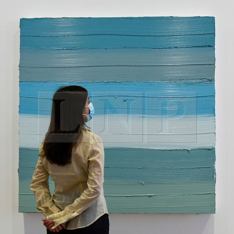 """© Licensed to London News Pictures. 16/06/2020. LONDON, UK. A staff member wearing a facemask views """"Untitled"""", 2019, by Jason Martin on the opening day of a new exhibition """"Art Basel at Ely House"""" taking place at Galerie Thaddaeus Ropac in Mayfair.  The commercial gallery has implemented social distancing guidelines for visitors for its reopening after coronavirus pandemic lockdown restrictions were relaxed by the UK government.  The exhibition runs 16 June to 31 July 2020.  Photo credit: Stephen Chung/LNP"""