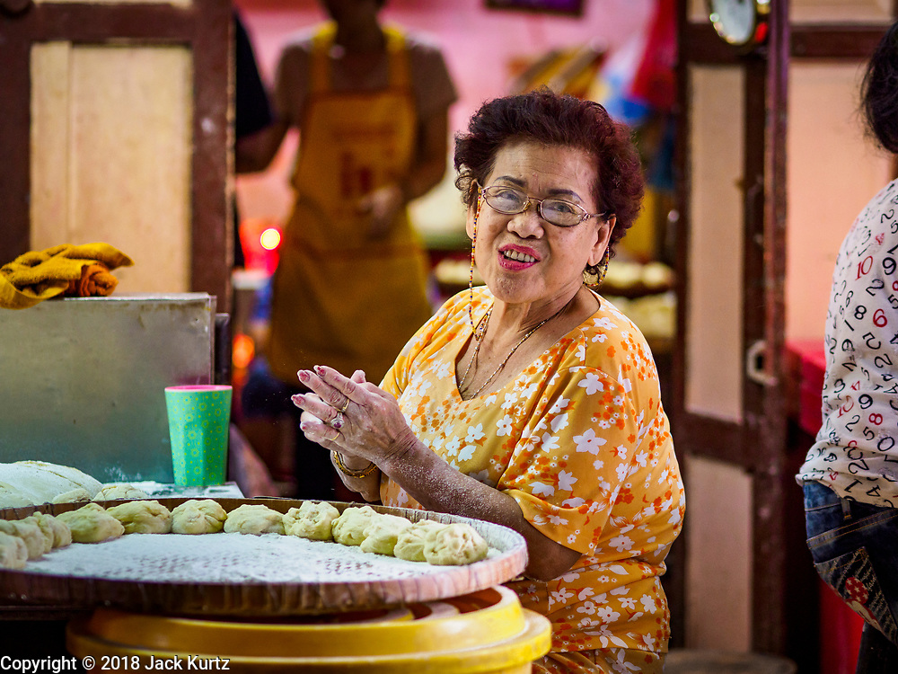 """12 FEBRUARY 2018 - BANGKOK, THAILAND:  A woman hand forms steamed buns in a home that makes steamed Chinese buns, called """"bao"""" in the Chinatown neighborhood of Bangkok. Bao are eaten at midnight on the Lunar New Year and served to guests during New Year's entertaining. Lunar New Year, also called Tet or Chinese New Year, is 16 February this year. The coming year will be the Year of the Dog. Thailand has a large Chinese community and Lunar New Year is widely celebrated in Thailand, especially in Bangkok and large cities with significant Chinese communities.   PHOTO BY JACK KURTZ"""