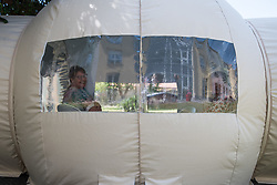 A woman visits her mother in a bubble at Fondation Shadet Vercoustre nursing home on May 27, 2020 in Bourbourg near Gravelines, France, where a double entry bubble has been installed to allow visits without risk of contamination, as part of a prophylactic measure against the spread of the Covid-19 disease caused by the novel coronavirus. Relatives and residents each enter the tent through a different entrance to find themselves in the same room, separated by a transparent plastic canvas. These bubbles were originally designed for tourism by the company. Photo by Julie Sebadelha/ABACAPRESS.COM