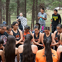 Head Coach Wilbert Nezz, bottom left, leads the Lady Bengals runners in prayer before they start the scrimmage. Many of the high schools in the Mckinley County area participated in an early season run to loosen their legs before the seasons begins. The scrimmage was held in McGaffey, NM.