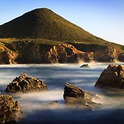 The incoming tide surrounds coastal boulders along the coast of Big Sur near Monterey, California.