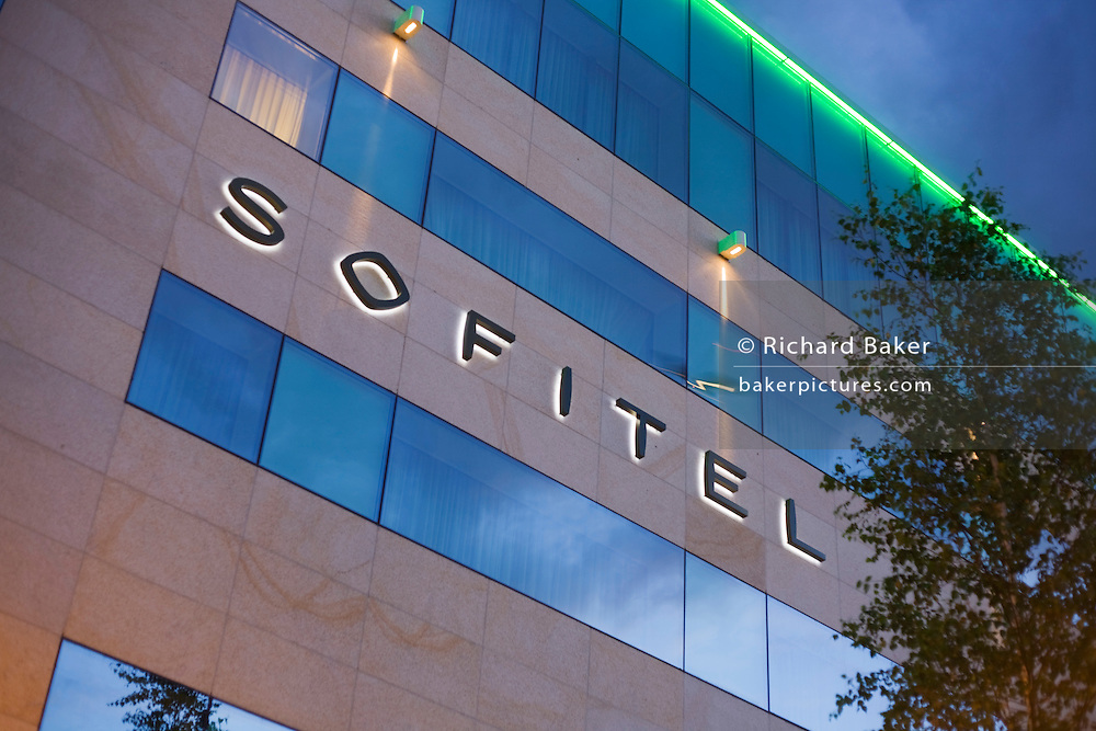 Reflected in the windows of hotel chain Sofitel, a blurred climbing aircraft takes-off from Heathrow airport's Terminal 5.