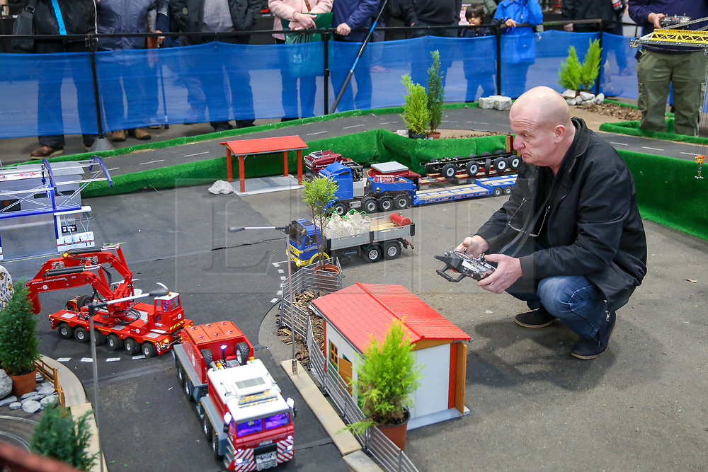 © Licensed to London News Pictures. 17/01/2020. London, UK. A member of the Ayimat with a remote control drives a building truck at the London Model Engineering Exhibition at Alexandra Palace.<br /> Enthusiasts and hobbyists visit the annual London Model Engineering Exhibition at Alexandra Palace in north London. Clubs and societies are exhibiting spectrum of modelling from traditional model engineering, steam locomotives and traction engines through to the more modern gadgets including trucks, boats, aeroplanes and helicopters with nearly 2,000 models constructed by their members. Photo credit: Dinendra Haria/LNP