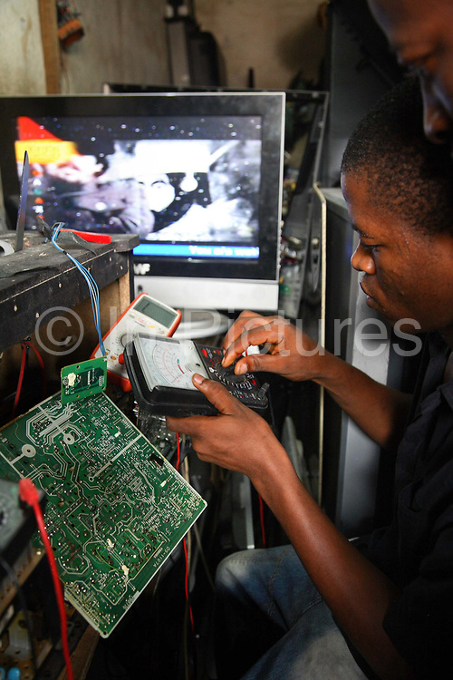 Alaba International Market.  A young man is fixing and testing old broken tvs.<br /> New and old - and a lot of non-working electronic goods such as TVs and computers come in to the market via Lagos harbour from the US, Western Europe and China. This picture is part of an undercover investigation by Greenpeace and Sky News.  A TV-set originally delivered to a municipality-run collecting point in UK for discarded electronic products was tracked and monitored by Greenpeace using a combination of GPS, GSM, and an onboard radiofrequency transmitter placed inside the TV-set.  The TV arrived in Lagos in container no 4629416 and was found in Alaba International Market and bought back by Greenpeace activist. The TV was subsequently brought back to England and used as proof of illegal export of electronic waste. A number of individual are currently on trial in London in connection with illegal exports(Nov 2011)