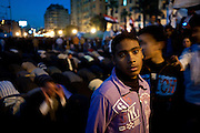 An Egyptian boy stands amid the throng while rows of adult men pray behind him. Thousands of protesters camped out in Tahrir Square in February 2010, calling for the ouster of President Hosni Mubarak.