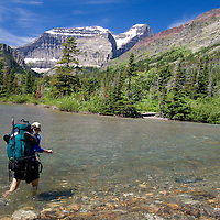 Mount Cleveland hangs in the distance as backpacker Matt Aronson crosses the Mokowanis River at the outlet of Cosley Lake in Glacier National Park.