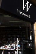 The Fleet Street branch of bookseller Waterstone's has its stock of covers and titles on display in afternoon sunlight. The store's logo and brand name is overhead at the shop's entrance and sunlight shines onto the lower shelves containing the literature on sale. Waterstone's is a British book specialist established in 1982 by Tim Waterstone that employs around 4,500 staff throughout the United Kingdom and Europe. As well as the Waterstone's brand, the group owns the London bookseller Hatchards, founded in 1797 and Irish store Hodges Figgis, founded in 1768, retaining these names due to their historical connections.