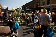 Buyers and sellers at East London's famous Sunday flower market on Columbia Road. Punters come here from the early hours to snatch up the best of the plants on offer, and latecomers also can snap up a few last minute bargains. Columbia Road os one of four local Sunday markets in this area of the East End of London.