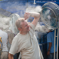 Pedestrians cool themselves down with water spray fans in the summer heat in Budapest, Hungary on July 13, 2011. ATTILA VOLGYI