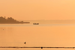 Silhouette of fishermen with boat in Chiemsee lake, Bavaria, Germany