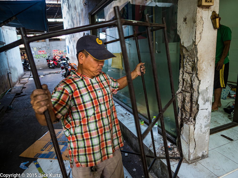31 DECEMBER 2015 - BANGKOK, THAILAND: A demolition worker carries scavenged metal past a beauty shop in Bang Chak Market after the shop was closed. The market is supposed to close permanently on Dec 31, 2015. The Bang Chak Market serves the community around Sois 91-97 on Sukhumvit Road in the Bangkok suburbs. About half of the market has been torn down. Bangkok city authorities put up notices in late November that the market would be closed by January 1, 2016 and redevelopment would start shortly after that. Market vendors said condominiums are being built on the land.          PHOTO BY JACK KURTZ