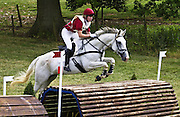 Young man rides a grey mare horse cross country  at eventing competition, Oxfordshire, United Kingdom