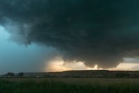 """Near Kinsey, Montana, I found myself in between a wall cloud from a stationary supercell and an advancing gust front from an MCS. Eventually the gust front overtook the wall cloud and everything merged together. At this point it was very windy with lots of dust in the air, but I had to get a couple last shots before the rain started. I was glad I wasn't in the precipitation core on the left since 2.5"""" hail and flooding was reported there."""