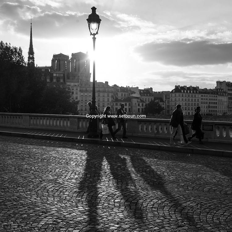 France. Paris. 4th district. pedestrians on the  Pont louis Phillipe bridge  over the seine river between le Marais and Saint louis island, in the distance Notre dame de paris cathedral.  /  le pont louis Phillipe traverse la seine du Marais a l ile saint Louis