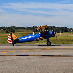Lancaster, PA, USA - August 22, 2015: Yellow biplane ready for takeoff at the Lancaster Airport Community Days air show.