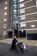 Muslim man pushes his baby in a pram near to council flats in Tower Hamlets, East London. Many people are at risk of losing their homes in London with the introduction of new benefit rules, which may push many people renting or who own council apartments out of the city. Tower Hamlets is a poor and over populated borough with many people living in small homes in high rise apartment blocks.