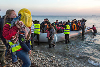 LESVOS, GREECE - FEBRUARY 09: Volunteers help refugees to get off a dinghy after their arrival on a beach in Lesvos from the Turkish coast on February 09, 2015 in Lesvos, Greece. Photo: © Omar Havana. All Rights Are Reserved