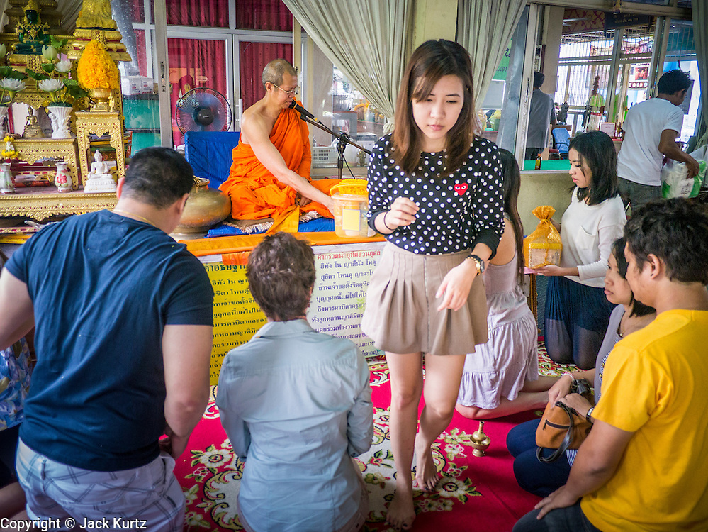 24 FEBRUARY 2013 - BANGKOK, THAILAND: A family receives blessings from a Buddhist monk at Wat Hua Lamphong. Wat Hua Lamphong is a Royal Buddhist temple, third class, in the Bang Rak District of Bangkok, Thailand. It is located on Rama IV Road, approximately 1km from the city's main Hua Lamphong railway station. An entrance to Sam Yan Station on the Bangkok metro (subway) is located outside the main entrance to the temple compound on Rama IV. Wat Hua Lamphong was renovated in 1996 to mark the 50th anniversary of the ascension to the throne of King Bhumibol Adulyadej (Rama IX) in 1996. The royal seal of what became known as the Kanchanapisek, or Golden Jubilee, year, showing two elephants flanking a multi-tiered umbrella, are featured in the temple's remodeling.     PHOTO BY JACK KURTZ