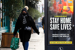 "© Licensed to London News Pictures. 09/01/2021. London, UK. A woman wearing a protective face covering walks past the Government's ''Stay Home, Save Lives' Covid-19 publicity campaign poster in north London, as the number of cases of the mutated variant of the SARS-Cov-2 virus continues to spread around the country. The message in the advertising campaign poster asks people to 'reduce contact to reduce the spread' and Prime Minister Boris Johnson has said that the public should ""stay at home"". Photo credit: Dinendra Haria/LNP"